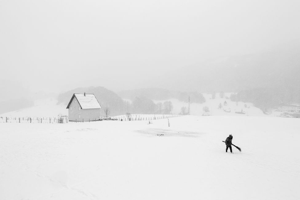 In the North of Montenegro a shepherd is walking to his herd of sheep with a self made broom in his hand. The broom was used to wipe off the snow lying on the back of the sheep.