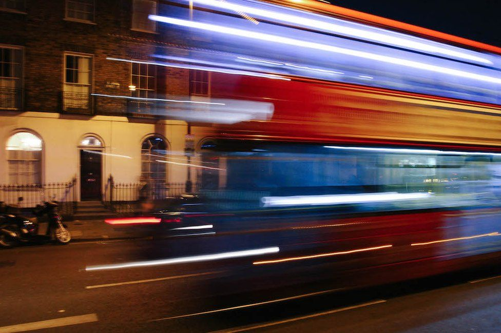 A blurred bus passes Islington town houses
