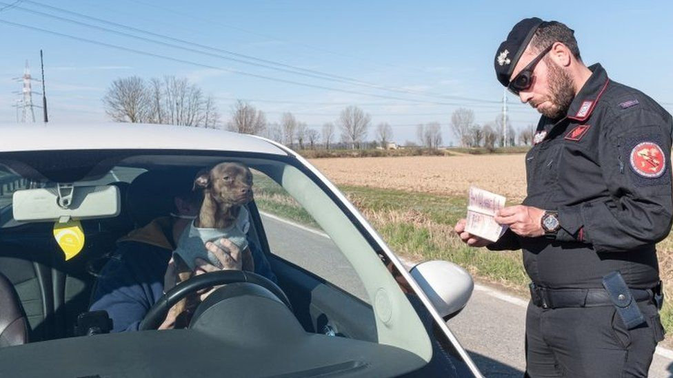 A police officer checks documents of a man in a car at a checkpoint in San Fiorano, Italy. Photo: 8 March 2020