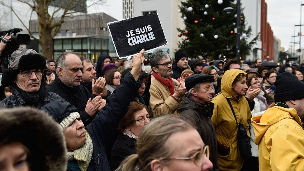 Mourners at a funeral for one of the Charlie Hebdo massacres