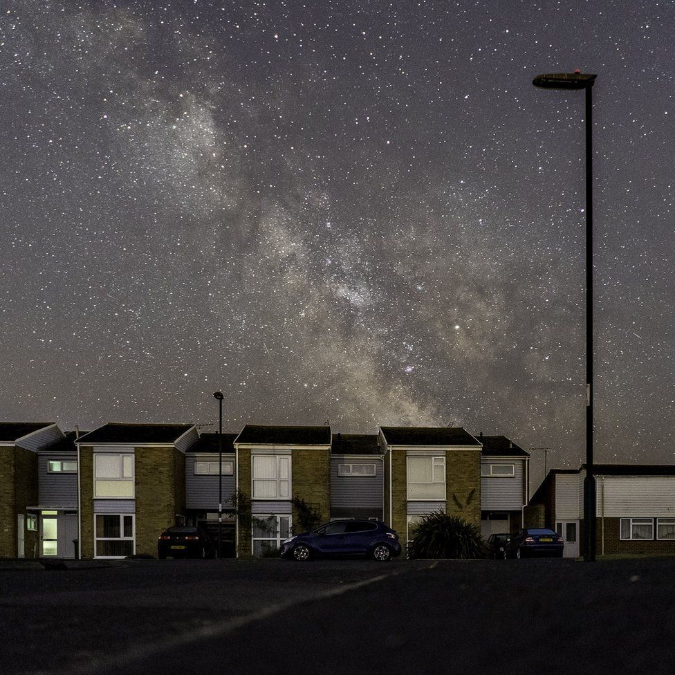 A silhouette of a lamppost reaches up from suburbia into the milky way