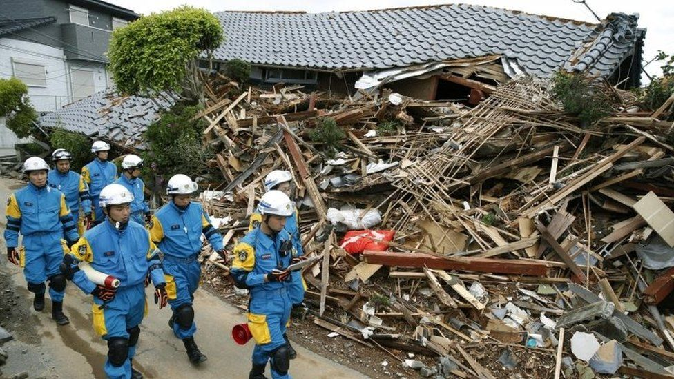 Police officers survey the damages in Mashiki, Kumamoto prefecture (17 April 2016)