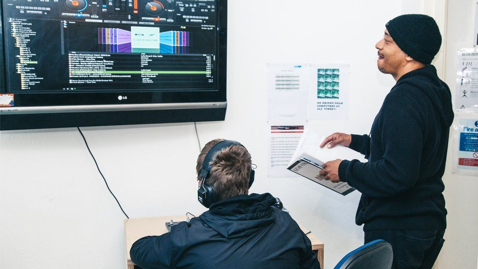 Student being taught in music production