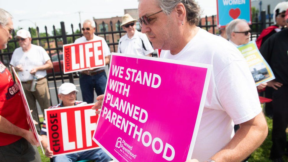 A supporter of Planned Parenthood stands near an anti-abortion demonstrators as they hold a protest outside the Planned Parenthood Reproductive Health Services Center in St. Louis, Missouri, May 31, 2019