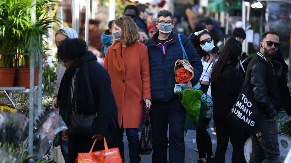 "Shoppers wearing a protective face masks visit Columbia Road flower market in east London on Mother""s Day, March 22, 2020. - Up to 1.5 million vulnerable people in Britain, identified as being most at risk from the coronavirus epidemic, should stay at home for at least 12 weeks, the government said Sunday"