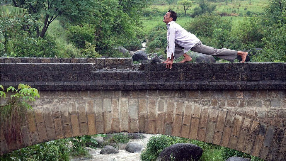 An Indian man performs yoga to mark the international Day of Yoga, in the rain at Baldhar Village, near Dharamsala, India 21 June 2017.