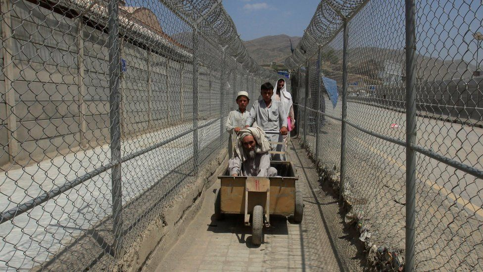 Men coming from Afghanistan move down a corridor between security fences at the border post in Torkham, Pakistan June 18, 2016