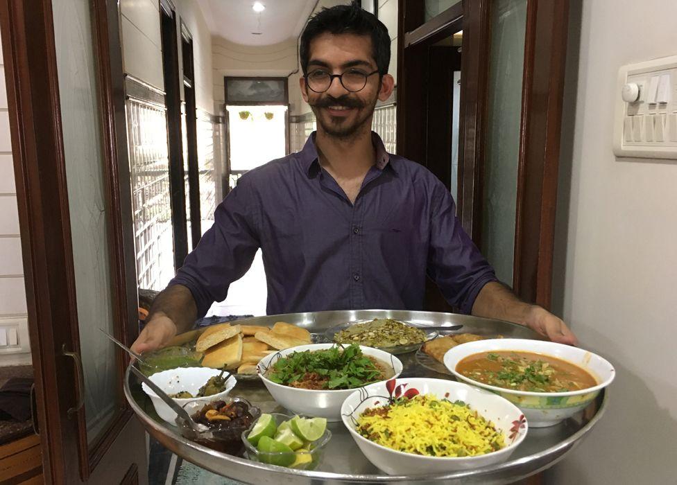 "Munaf Kapadia holding a large steel platter, or ""thaal"""