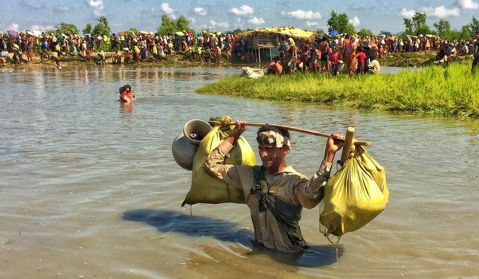 A Rohingya man wading in waist-deep water carries sacks and pots over his head, looking directly at the camera