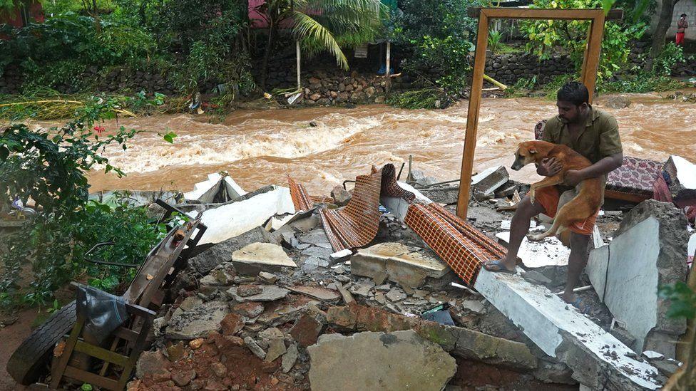 Житель несет собаку среди обломков своего разрушенного дома после внезапного наводнения, вызванного проливными дождями в Тодупуже, штат Керала, Индия, 16 октября 2021 г.