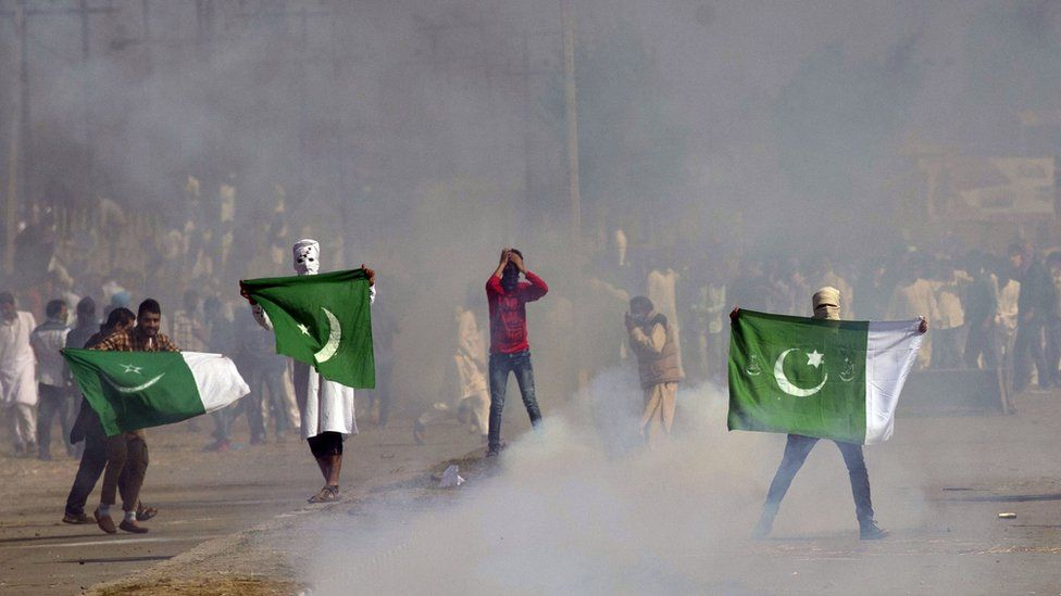 Masked Kashmiris hold the national flag of Pakistan during a protest outside Eidgha, a prayer ground, in Srinagar, Indian controlled Kashmir