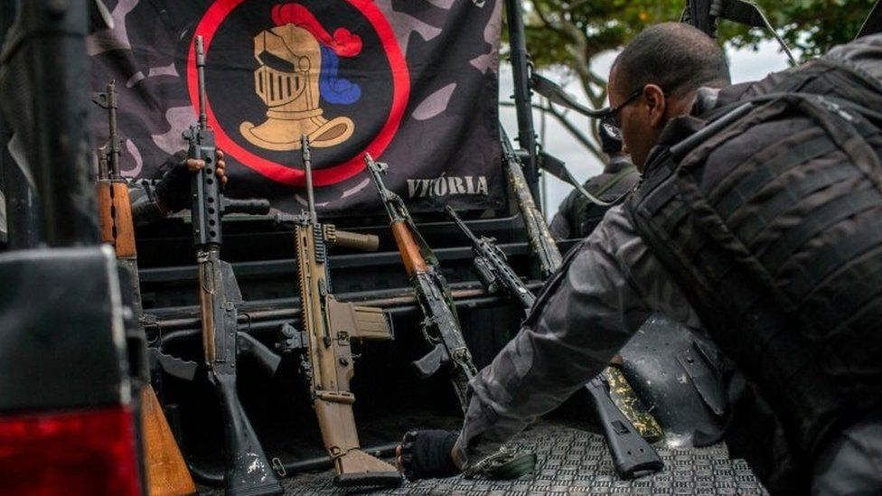 A member of the military police shows the weapons seized during a police operation in which they chased drug dealers escaping from Babilonia favela until catching them after a shootout in Vermelha beach at Urca neighbourhood, in Rio de Janeiro, Brazil, on June 8, 2018.