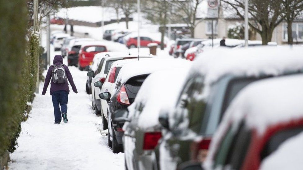 A woman walks through the snow in Penicuik, Midlothian.