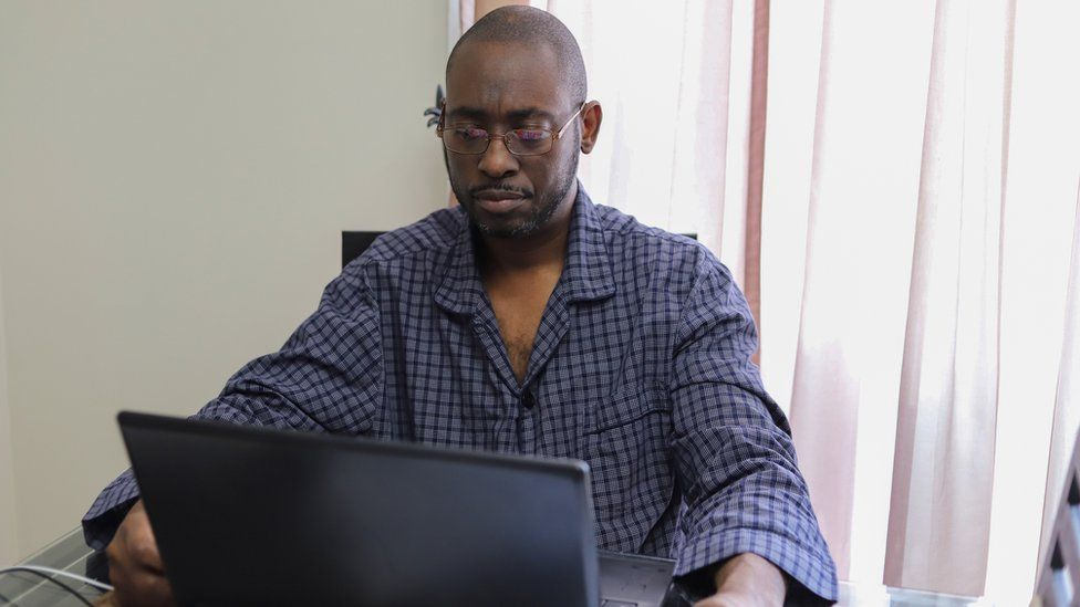 Man in pyjamas working from home