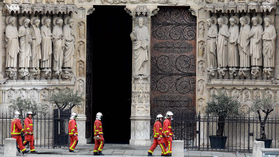 Firefighters walk in front of Notre-Dame
