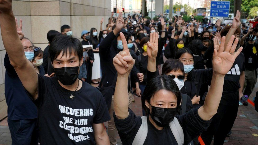 Protesters gesture outside West Kowloon Magistrates Court, where pro-democracy activists face charges related to national security, in Hong Kong