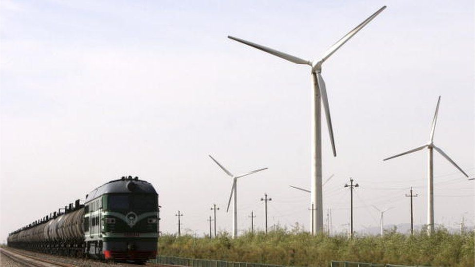A train runs past wind turbines at a wind power plant in Dabancheng, Xinjiang Uygur Autonomous Region, China