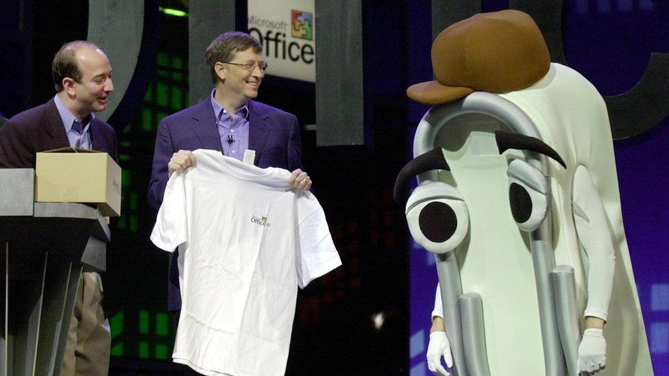 Bill Gates smiles holding a white t-shirt next to an actor wearing a giant Clippy foam suit