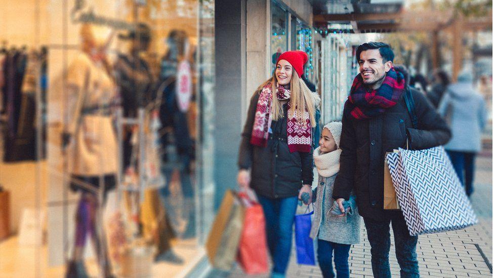 A family look at clothes through a shop window
