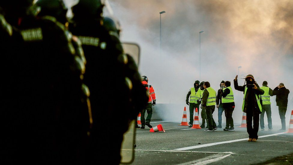 """People stand in front of gendarmes on Caen's circular road on November 18, 2018 in Caen, northwestern France, on a second day of action after a nationwide popular initiated day of protest called """"yellow vest"""" (Gilets Jaunes in French) movement"""