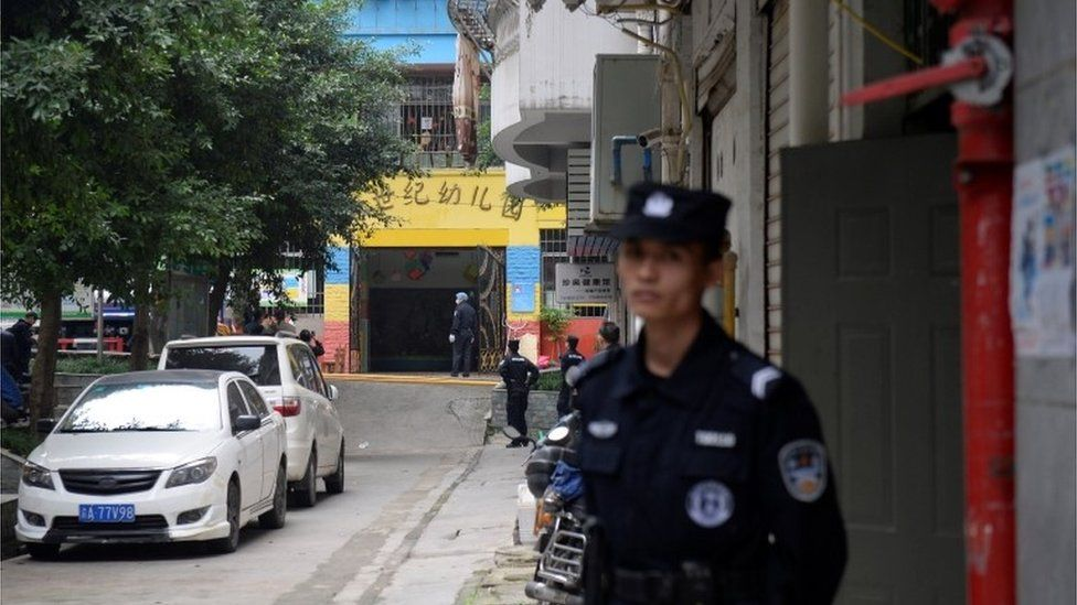 Police officers stand in the street outside the Chongqing kindergarten