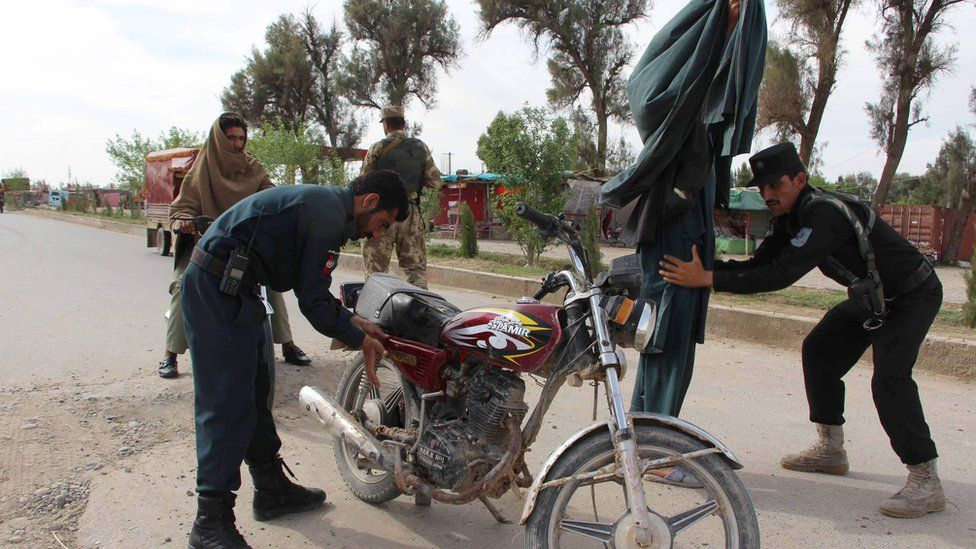 In this photograph taken on 23 March 2017, Afghan policemen search passengers at a checkpoint in Lashkar Gah