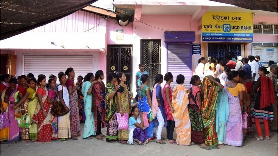 Indian villagers wait in a queue outside a bank to deposit and exchange 500 and 1000 rupee notes in Chandrapur Village, some 30 kms from Guwahati on November 15, 2016.