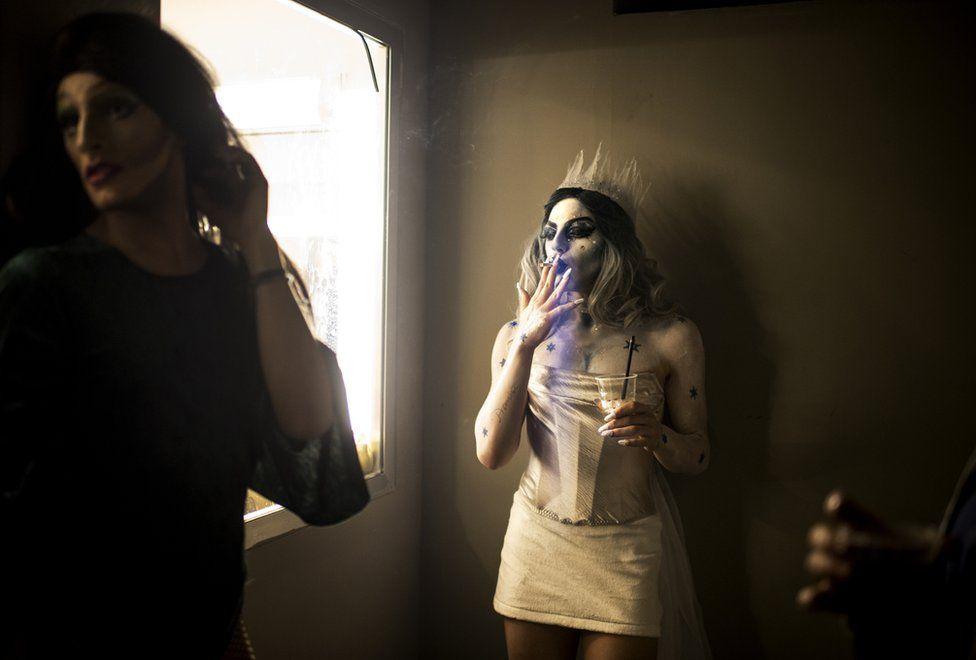 Elias dressed as drag queen Melanie Coxxx takes a cigarette break