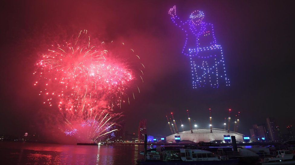 An image of Capt Sir Tom lit up the night sky during the virtual 2021 New Year celebrations over the Millennium Dome (O2 Arena) in London
