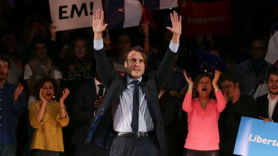 French presidential election candidate Emmanuel Macron waves on stage at the end of a campaign event in central London on February 21