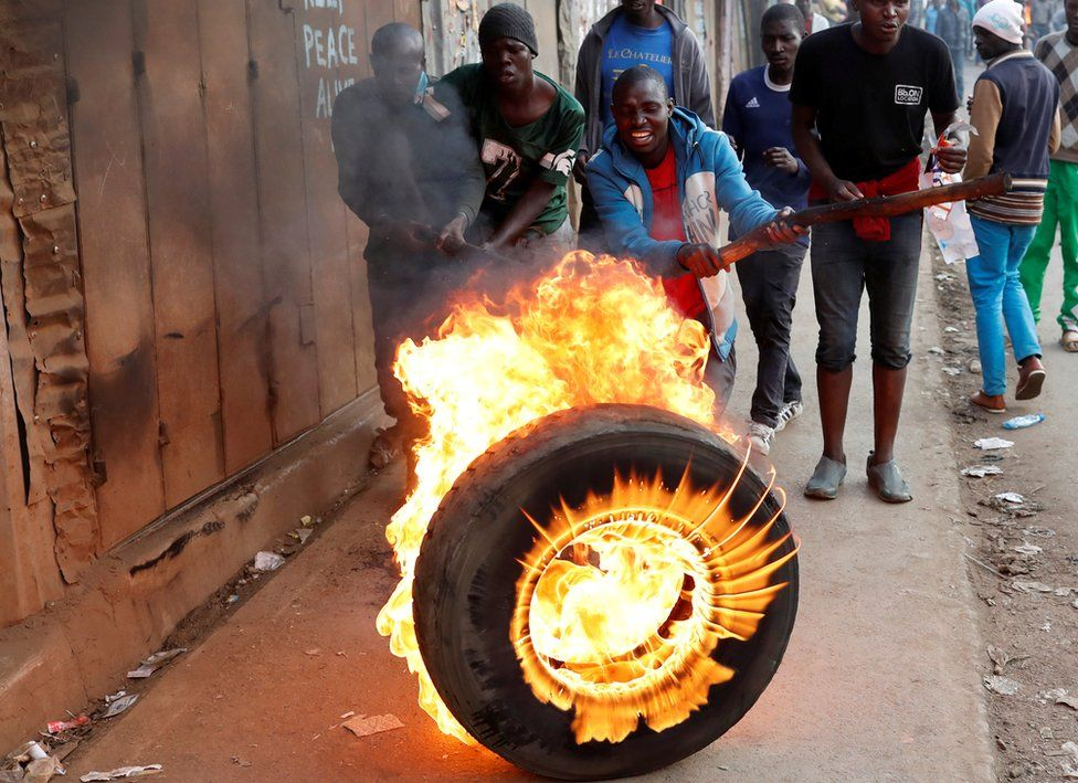 A man hits a flaming tyre with a stick