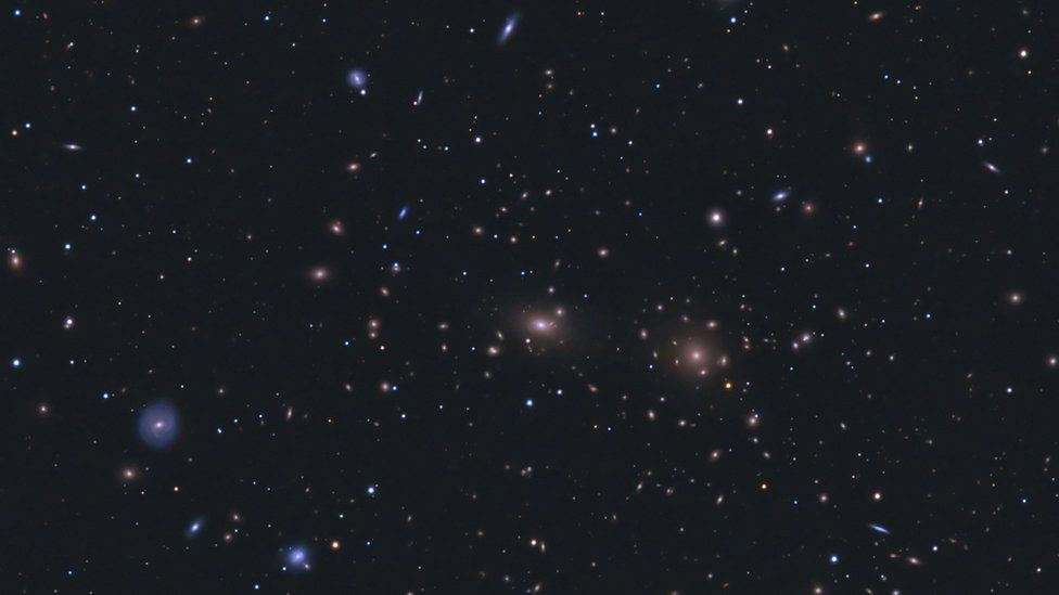 A star field with many galaxies visible, both blue and white. They are somewhat clustered towards the centre of the image.