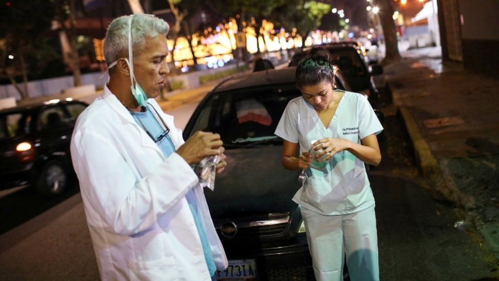 Doctors Carlos Martinez and Maria Martinez eat a snack while they wait in line to get fuel at a gas station, during a nationwide quarantine due to the coronavirus disease (COVID-19) outbreak, in Caracas, Venezuela April 7, 2020.