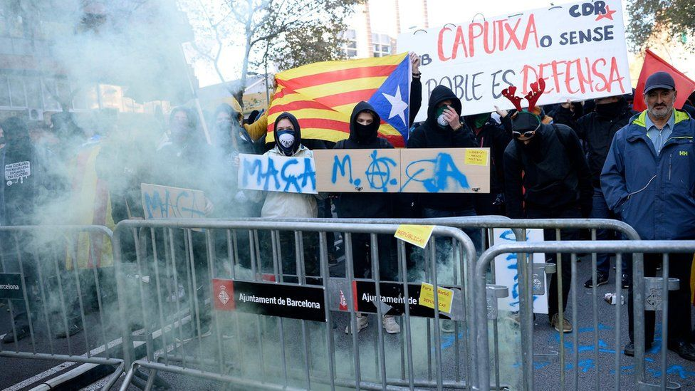 Catalan pro-independence protesters stand behind crowd control barricades during a demonstration in Barcelona on December 21, 2018