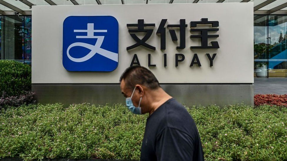 A man walks past an Alipay sign outside Ant Group's building in Shanghai.
