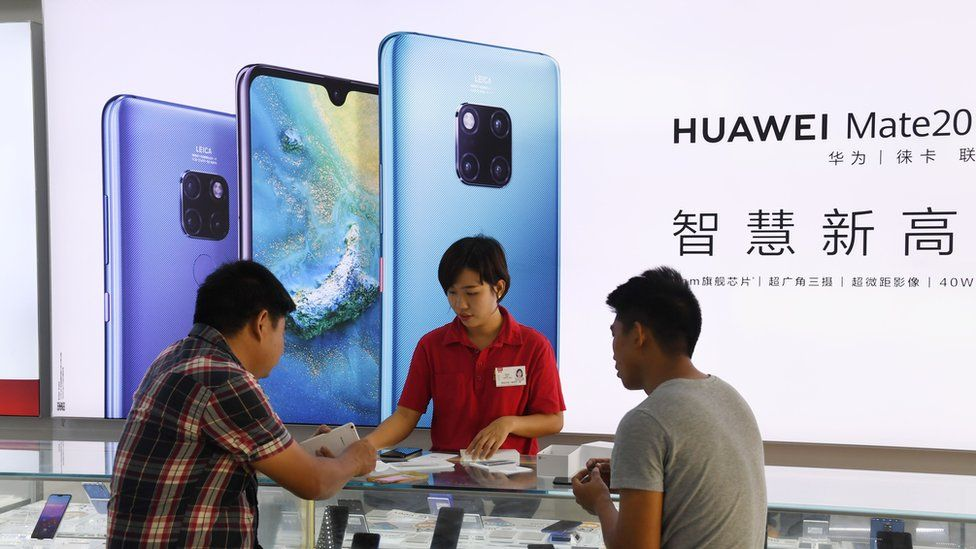 A store clerk serves customers at a Huawei store