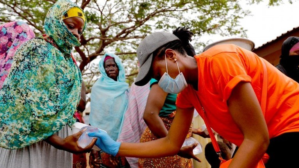 A volunteer distributes cooked food and water to the underprivileged and homeless, as Ghana enforces a partial lockdown in Accra and Kumasi in efforts to slow the spread of the coronavirus disease (COVID-19), in Accra, Ghana. April 4, 2020