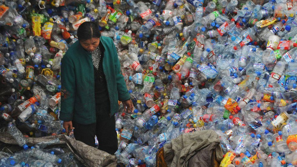 A woman sorts plastic at a dump in China. Millions of tonnes of plastics are wasted globally every year.