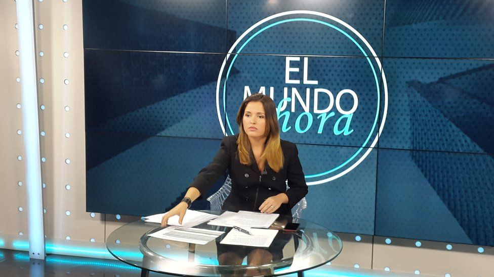A presenter sits on the set of Canal Caribe's El Mundo ahora