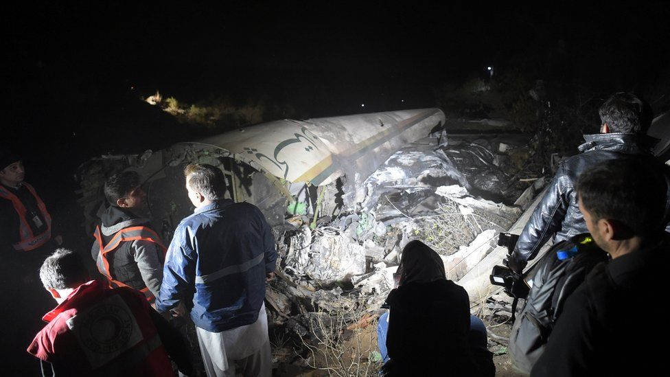 Pakistani officials of Pakistan International Airlines (PIA) look at the wreckages of crashed PIA passenger plane Flight PK661 at the site