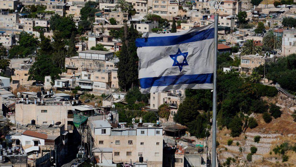 An Israeli flag flies above East Jerusalem's Sheikh Jarrah neighbourhood