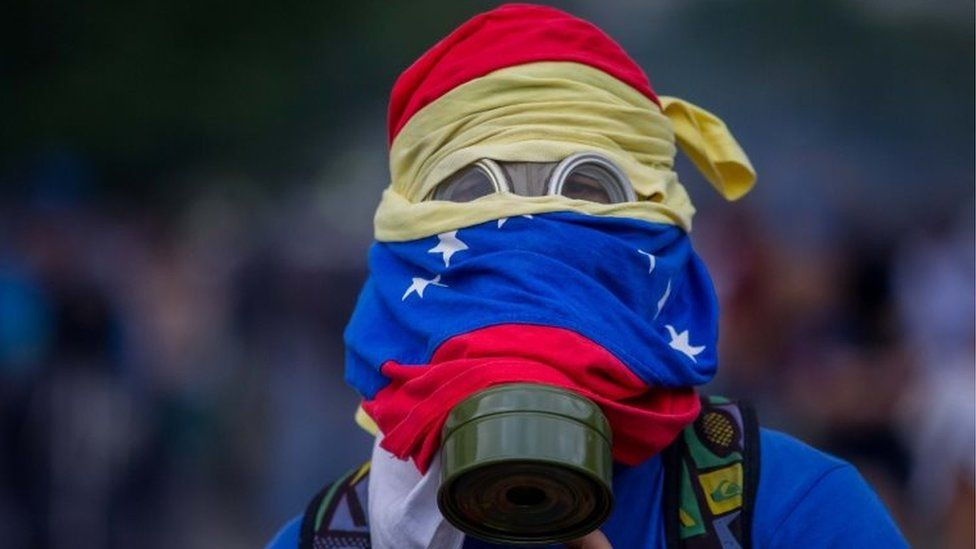 A protester wearing a gas mask is seen during clashes with the Venezuelan National Guard (GNB) in Caracas, Venezuela, on 10 April 2017.