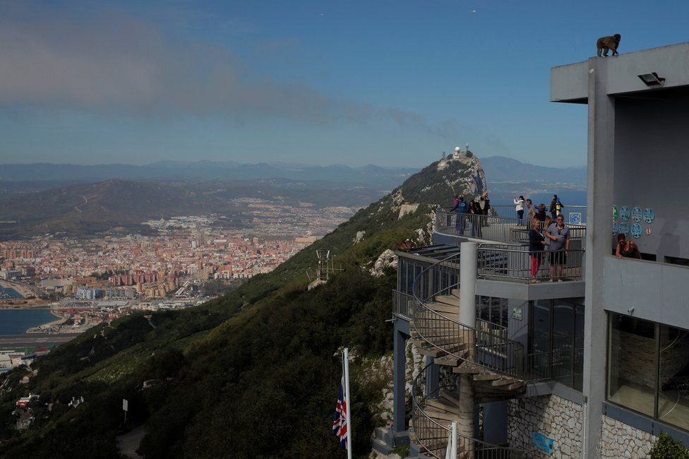 Tourists stand at a terrace on the top of the Rock in the British overseas territory of Gibraltar, historically claimed by Spain, 29 March