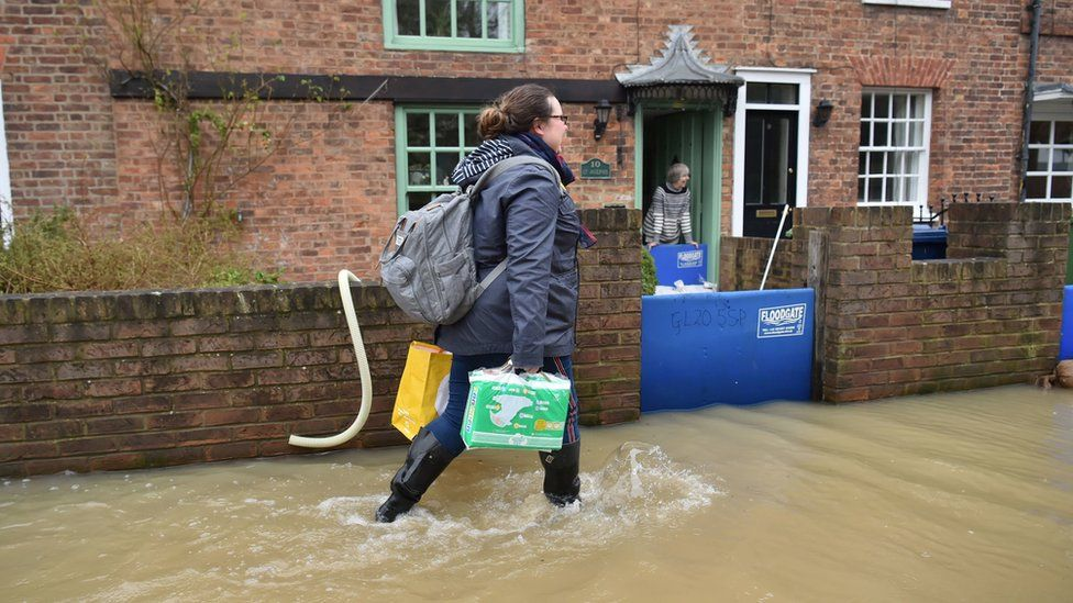 A woman wading through floods in Tewkesbury, Gloucestershire