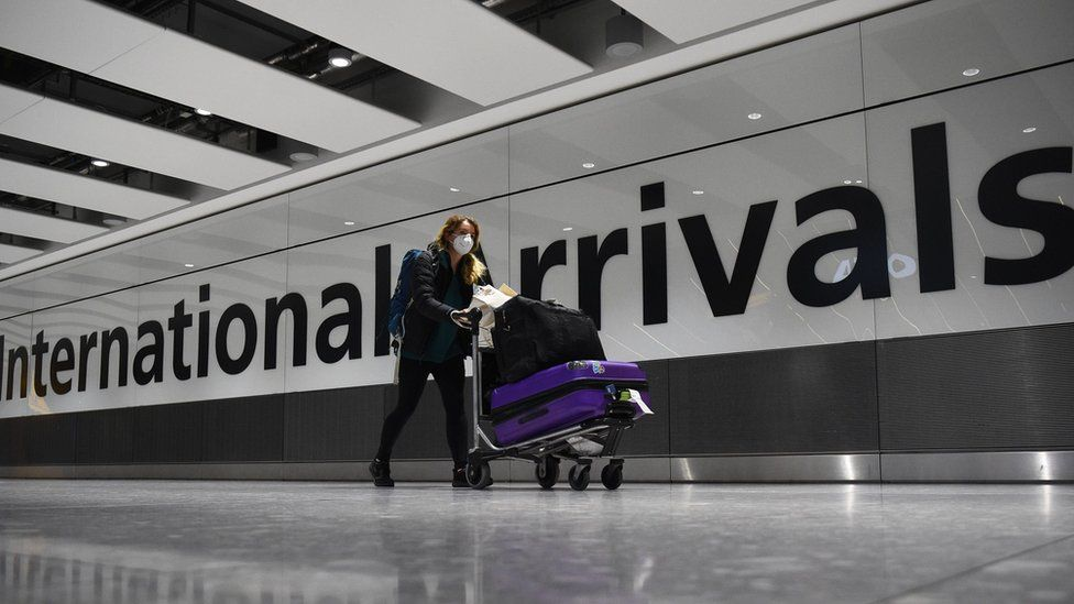 "A passenger pushes luggage through the Arrival Hall of Terminal 5 at London""s Heathrow Airport"