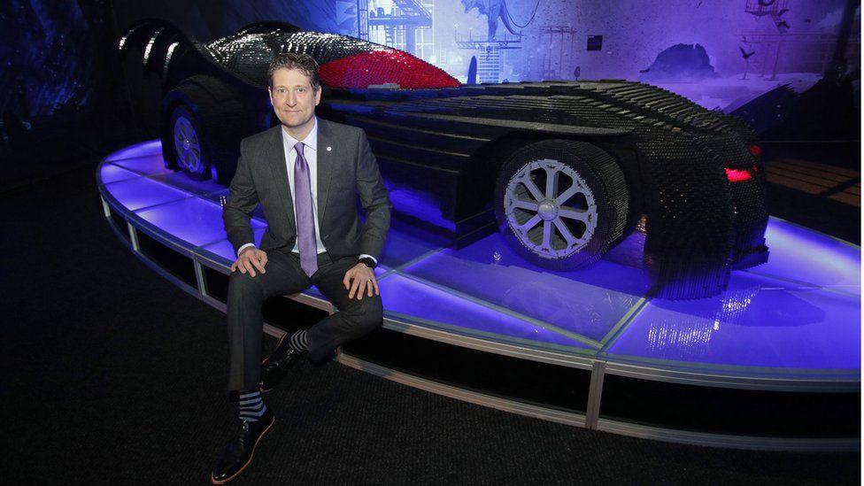 Artist Nathan Sawaya poses with a model of the Batmobile