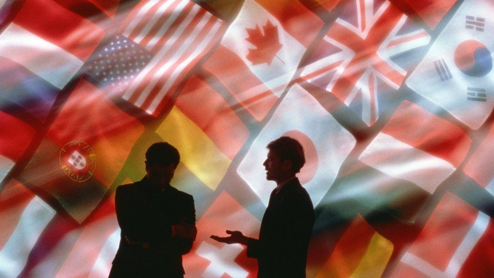 Businessmen talking in front of flags
