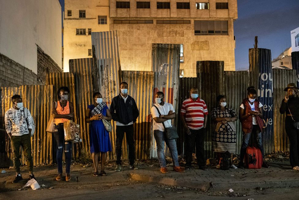 Commuters wait for a bus ahead of the night time curfew in Nairobi, on 27 March 2021