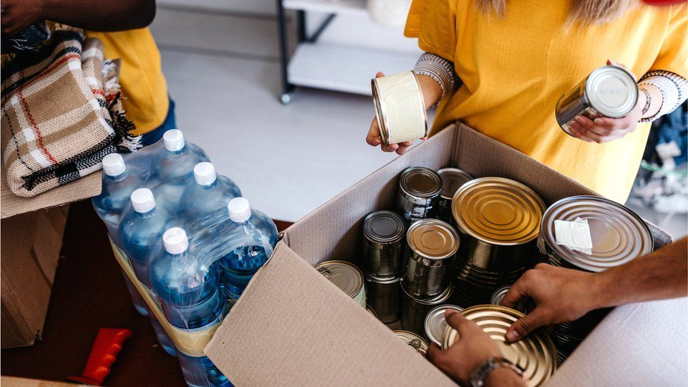 Boxes of tinned food and packets of water bottles at a food bank