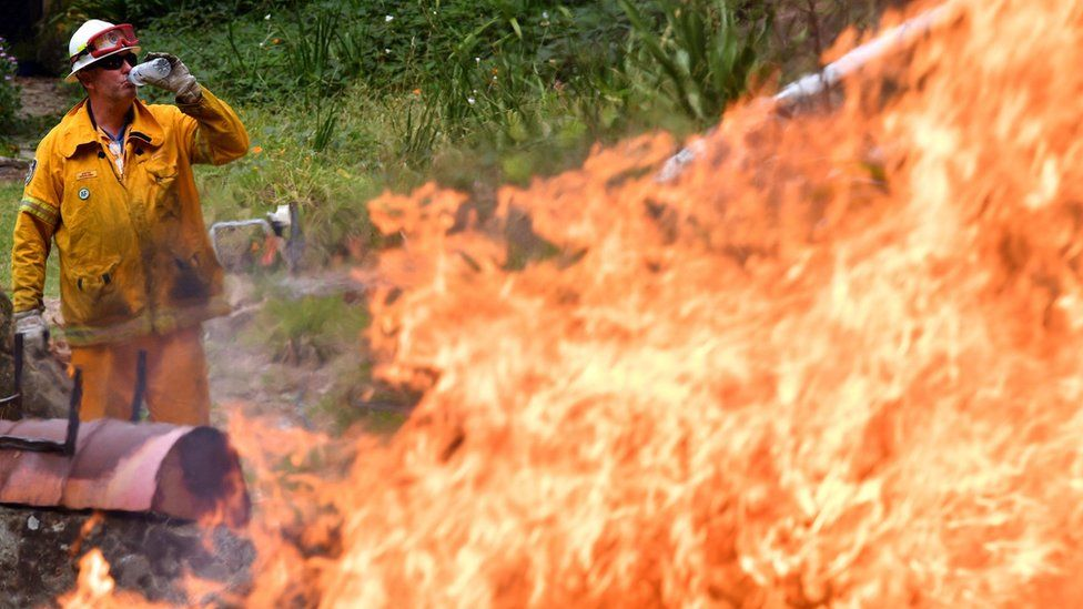 A firefighter drinks water in front of a raging bushfire north of Sydney on Monday